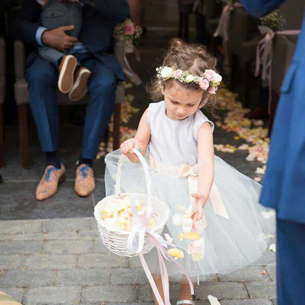 Bruidsmeisje in lichtgrijs jurkje met tule die bloemblaadjes strooit