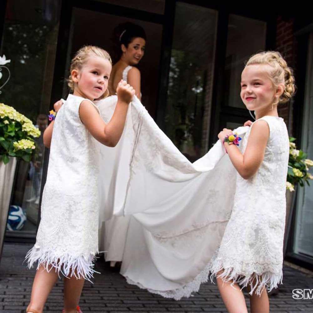 Twee bruidsmeisje die sleep tillen in bruidsmeisjes jurkjes met veertjes en kant