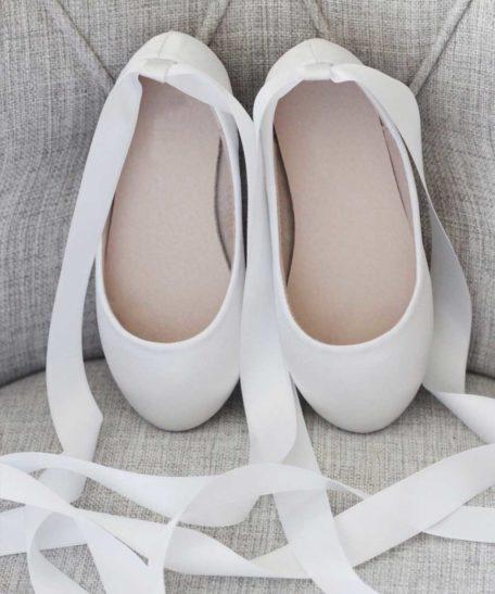 Bruidsmeisjes schoenen in ivoor met lint om de benen van satijn